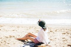 Stylish hipster girl in hat sitting on beach and tanning near sea waves. Summer vacation. Happy boho woman relaxing and enjoying. Sunny warm day at ocean. Space stock image
