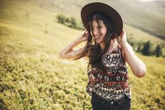 Stylish hipster girl in hat traveling on top of sunny mountains and smiling. Portrait of happy young woman with beautiful hair royalty free stock images