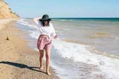 Stylish hipster girl in hat walking on beach and smiling. Summer vacation. Happy young boho woman relaxing and enjoying sunny warm. Day at tropical island and royalty free stock photos