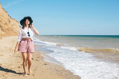 Stylish hipster girl in hat walking on beach and smiling. Summer vacation. Happy young boho woman relaxing and enjoying sunny warm. Day at tropical island and stock photo