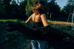 Stylish hipster girl having fun in sunny park in amazing sunbeams, atmospheric moment. Fashionable cool woman dancing and moving royalty free stock photo