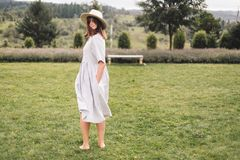 Stylish hipster girl in linen dress and hat having fun at lavender field and relaxing in mountains. Bohemian woman smiling and. Enjoying vacation. Atmospheric royalty free stock photography