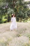 Stylish hipster girl in linen dress and hat relaxing in lavender field near tree. Happy bohemian woman enjoying summer vacation in stock images