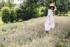 Stylish hipster girl in linen dress and hat relaxing in lavender field near tree. Happy bohemian woman enjoying summer vacation in stock photo