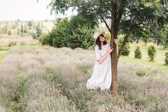 Stylish hipster girl in linen dress and hat relaxing in lavender field near tree. Happy bohemian woman enjoying summer vacation in royalty free stock photo