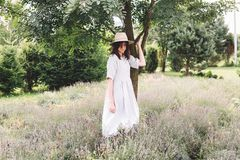 Stylish hipster girl in linen dress and hat relaxing in lavender field near tree. Happy bohemian woman enjoying summer vacation in stock photography