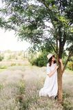 Stylish hipster girl in linen dress and hat relaxing in lavender field near tree. Happy bohemian woman enjoying summer vacation in royalty free stock photography