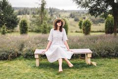 Stylish hipster girl in linen dress and hat sitting on bench at lavender field and relaxing in the morning. Happy bohemian woman. Enjoying vacation in mountains royalty free stock photography