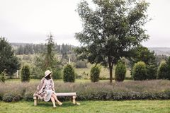 Stylish hipster girl in linen dress and hat sitting on bench at lavender field and relaxing in the morning. Happy bohemian woman. Enjoying vacation in mountains stock images