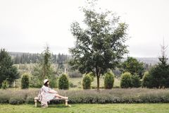 Stylish hipster girl in linen dress and hat sitting on bench at lavender field and relaxing in the morning. Happy bohemian woman. Enjoying vacation in mountains royalty free stock photos