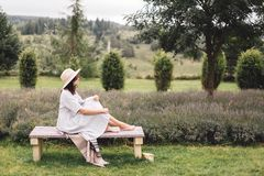 Stylish hipster girl in linen dress and hat sitting on bench at lavender field and relaxing in the morning. Happy bohemian woman. Enjoying vacation in mountains stock photos