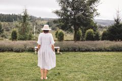 Stylish hipster girl in linen dress and hat standing at lavender field and relaxing in mountains. Back view. Bohemian woman. Smiling and enjoying vacation royalty free stock images