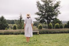 Stylish hipster girl in linen dress and hat standing at lavender field and relaxing in mountains. Back view. Bohemian woman. Smiling and enjoying vacation stock photos