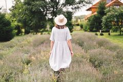 Stylish hipster girl in linen dress and hat walking in lavender field and relaxing. Happy bohemian woman enjoying lavender aroma. Back view. Atmospheric calm stock photography