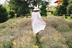 Stylish hipster girl in linen dress and hat walking in lavender field and relaxing. Happy bohemian woman enjoying lavender aroma. Back view. Atmospheric calm stock image