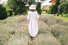 Stylish hipster girl in linen dress and hat walking in lavender field and relaxing. Happy bohemian woman enjoying lavender aroma. Back view. Atmospheric calm royalty free stock images