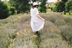 Stylish hipster girl in linen dress and hat walking in lavender field and relaxing. Happy bohemian woman enjoying lavender aroma. In summer mountains royalty free stock photography