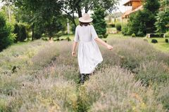 Stylish hipster girl in linen dress and hat walking in lavender field and relaxing. Happy bohemian woman enjoying lavender aroma. In summer mountains royalty free stock photo