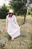Stylish hipster girl in linen dress and hat walking in lavender field and relaxing. Happy bohemian woman enjoying lavender aroma. In summer mountains stock image