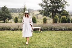 Stylish hipster girl in linen dress and hat walking at lavender field and relaxing in mountains. Bohemian woman smiling and. Enjoying vacation. Atmospheric stock image