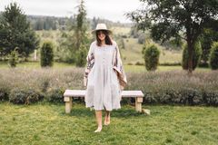 Stylish hipster girl in linen dress and hat walking at lavender field and relaxing in mountains. Bohemian woman smiling and. Enjoying vacation. Atmospheric stock images
