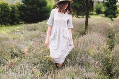 Stylish hipster girl in linen dress and hat walking in lavender field and smiling. Happy bohemian woman relaxing and enjoying. Lavender aroma. Atmospheric calm royalty free stock photography