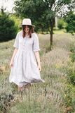 Stylish hipster girl in linen dress and hat walking in lavender field and smiling. Happy bohemian woman relaxing and enjoying. Lavender aroma. Atmospheric calm stock image