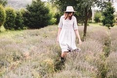 Stylish hipster girl in linen dress and hat walking in lavender field and smiling. Happy bohemian woman relaxing and enjoying. Lavender aroma. Atmospheric calm royalty free stock image