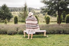 Stylish hipster girl in poncho, linen dress and hat posing at lavender field and relaxing in the morning. Bohemian woman enjoying. Vacation in mountains royalty free stock photo