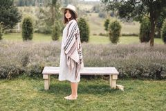 Stylish hipster girl in poncho, linen dress and hat posing at lavender field and relaxing in the morning. Bohemian woman enjoying. Vacation in mountains stock photography
