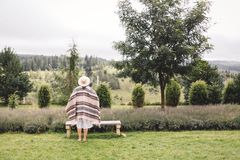 Stylish hipster girl in poncho, linen dress and hat posing at lavender field and relaxing in the morning. Bohemian woman enjoying. Vacation in mountains stock photos