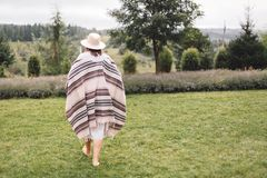 Stylish hipster girl in poncho, linen dress and hat walking at lavender field and relaxing in the morning. Bohemian woman enjoying. Vacation in mountains royalty free stock photos