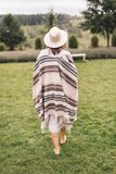 Stylish hipster girl in poncho, linen dress and hat walking at lavender field and relaxing in the morning. Bohemian woman enjoying. Vacation in mountains stock images