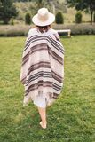 Stylish hipster girl in poncho, linen dress and hat walking at lavender field and relaxing in the morning. Bohemian woman enjoying. Vacation in mountains stock photo