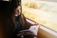 Stylish hipster girl reading book at window light in train. travelling by train concept. beautiful young woman holding paper book. Travel and transportation royalty free stock photo