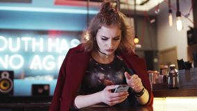 Stylish hipster girl with red lips using her phone in a cozy café, gets the message, looks disappointed, texts back stock video footage