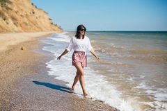 Stylish hipster girl relaxing on beach and having fun.  Happy young boho woman walking and smiling in sea waves in sunny warm day. On tropical island. Summer royalty free stock images