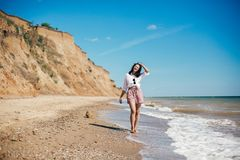 Stylish hipster girl relaxing on beach and having fun.  Happy young boho woman walking and smiling in sea waves in sunny warm day. On tropical island. Summer stock photo