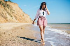 Stylish hipster girl relaxing on beach and having fun.  Happy young boho woman walking and smiling in sea waves in sunny warm day. On tropical island. Summer stock photography