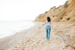 Stylish hipster girl running barefoot on beach at sea , back view. Happy fashionable boho woman relaxing at sandy cliff on. Tropical island. Travel and summer stock photography