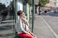 Stylish hipster girl sitting on bus stop in spring sunny day. fashionable woman tourist waiting for city transport.  Royalty Free Stock Images
