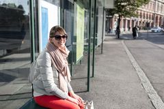 Stylish hipster girl sitting on bus stop in spring sunny day. fashionable woman tourist waiting for city transport.  Stock Image