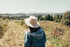 Stylish hipster girl travelling in sunny mountains. Woman in hat exploring and hiking on top of mountain on summer vacation. stock photo