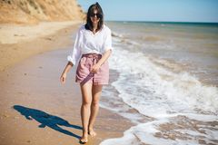 Stylish hipster girl  walking on beach and smiling. Summer vacation. Happy young boho woman relaxing and enjoying sunny warm day. At tropical island and blue royalty free stock image