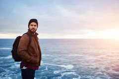 Stylish hipster guy enjoying vacations at the seashore in cold autumn day Royalty Free Stock Photography