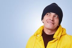 Stylish hipster guy wears fashionable yellow anorak and black hat, looks pensively aside, dreams about something pleasant, isolate. D over blue background royalty free stock photos