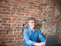 Young man freelancer working on his web site on portable laptop computer, sitting in modern interior against brick wall. royalty free stock image
