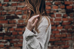 Stylish hipster gypsy woman posing in knitted sweater on backgro. Und of brick wall, holding hair. atmospheric sensual moment. boho country fashionable look Stock Photos