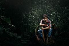 Stylish hipster lumberjack with ax in the sunny forest in mounta. Ins Royalty Free Stock Photos
