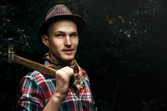 Stylish hipster lumberjack with ax in the sunny forest in mounta Royalty Free Stock Photo
